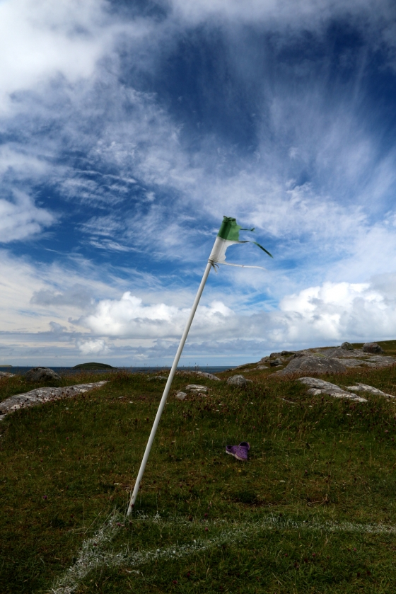 A bedraggled corner flag fighting the wind on the football pitch on Eriskay